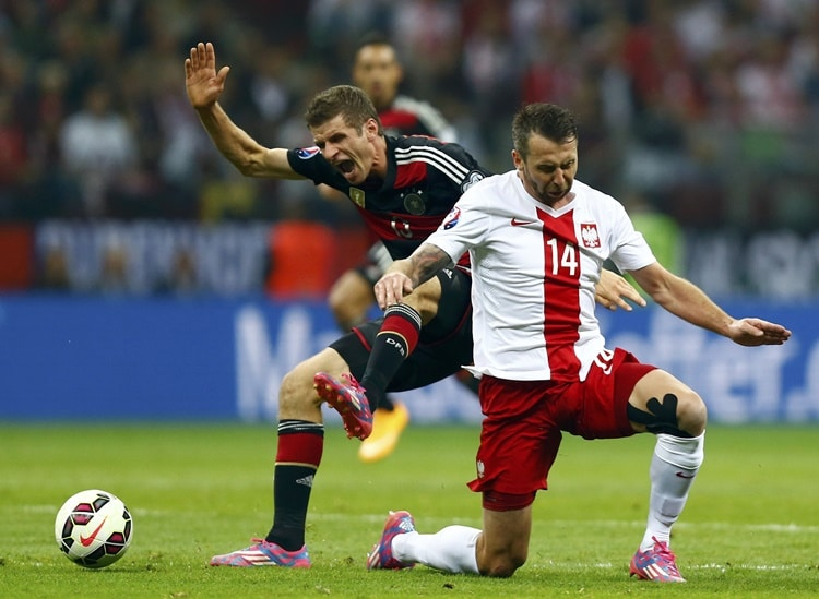 Germany's Thomas Mueller (L) challenges Poland's Jakub Wawrzyniak during their Euro 2016 group D qualifying soccer match at the National stadium in Warsaw October 11, 2014. REUTERS/Kacper Pempel (POLAND - Tags: SOCCER SPORT)